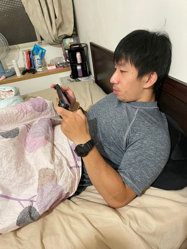 躺坐在床上滑手機
